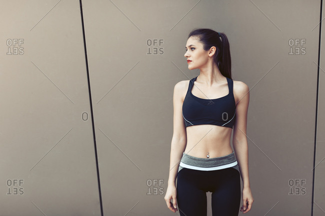 Portrait of athletic woman in sportswear with navel piercing against plain wall