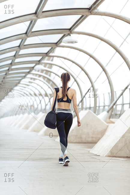 Rearview of athletic woman in sportswear carrying gym bag heading to workout