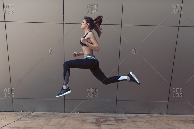 Athletic woman caught in mid air while jumping