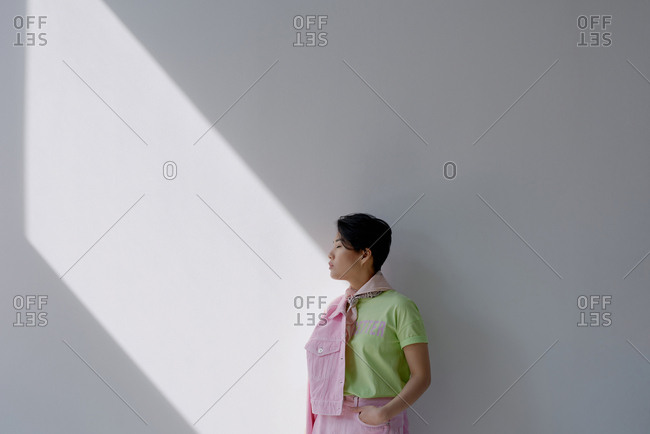Portrait of young Asian woman in stylish casual outfit standing with closed eyes against white wall illuminated by sun, copy space