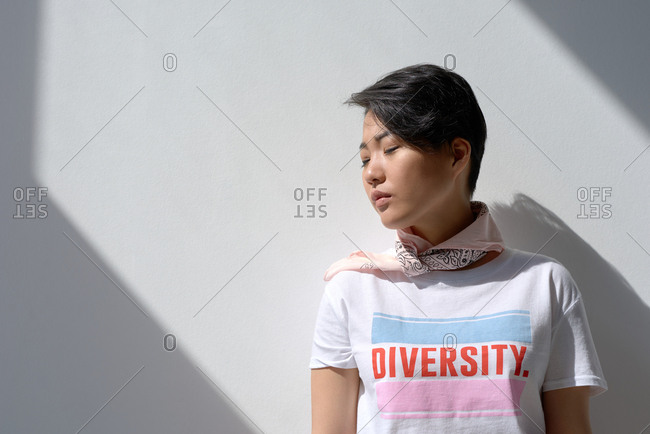Portrait of attractive Asian girl in t-shirt with lettering and kerchief on neck standing with closed eyes against white wall illuminated by sunlight