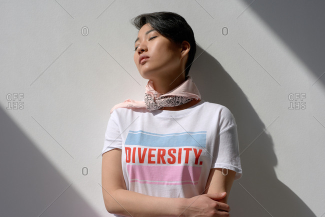 Portrait of attractive Asian girl in t-shirt with lettering and kerchief leaning on white wall with her eyes closed