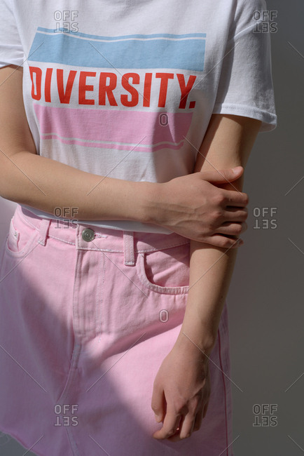 Conceptual shot of unrecognizable woman wearing stylish casual T-shirt with lettering and denim skirt, bright sun illuminated her body