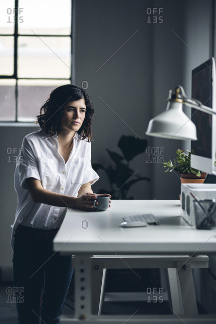 Hip business woman standing at a desk and drinking coffee in a modern office space