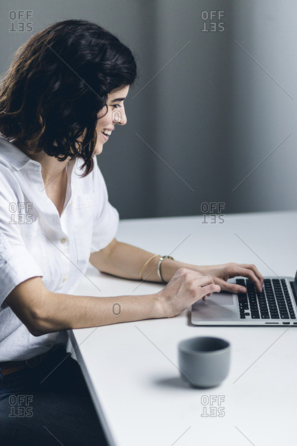 Creative female working on a laptop smiling in a neutral colored office
