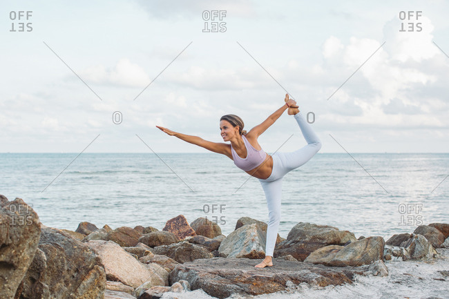 Woman doing yoga pose by the ocean