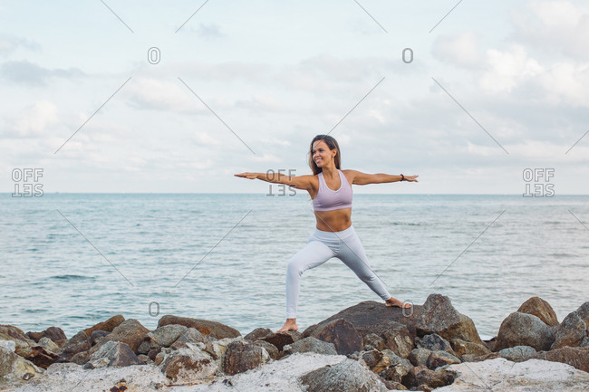 Woman doing yoga by the ocean