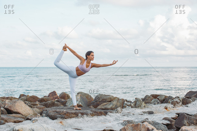 Woman practicing yoga next to the ocean