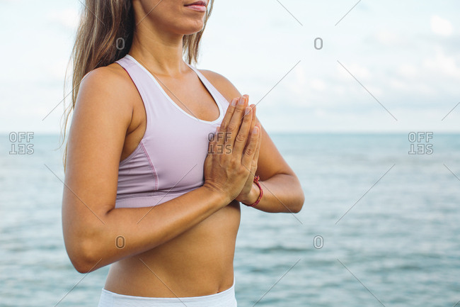 Close up of woman meditating by the ocean