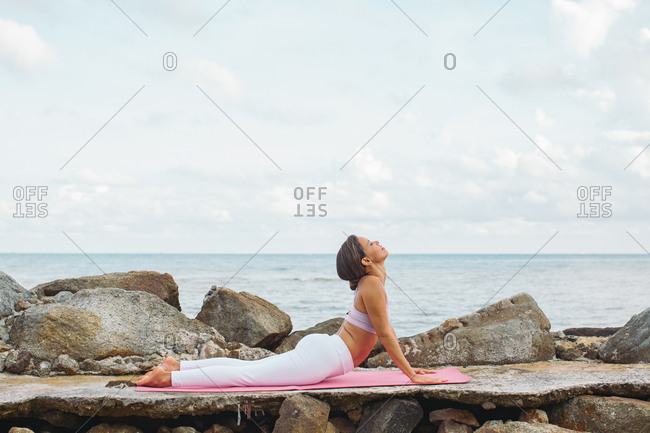 Woman doing yoga on a mat by the ocean
