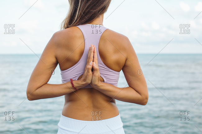 Close up of woman meditating with hands behind her back by the ocean