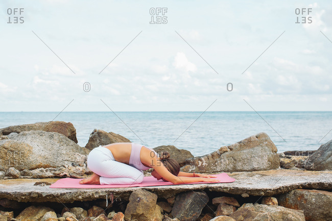 Woman practicing yoga on a mat by the ocean
