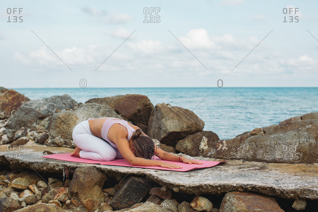 Woman doing yoga stretches on a mat by the ocean