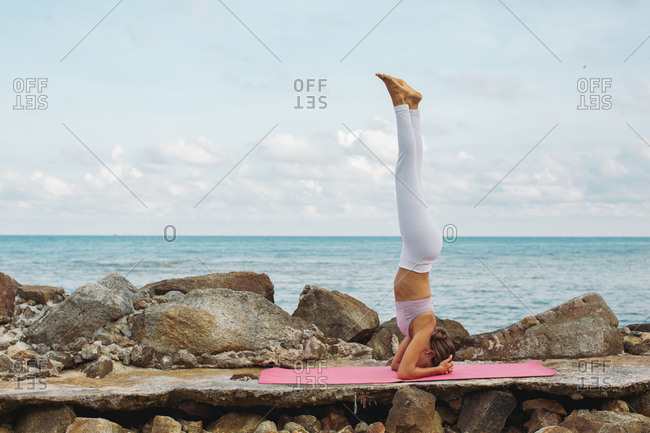 Woman doing headstand on a yoga mat by the ocean