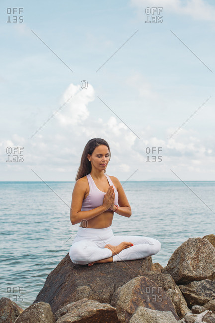 Woman meditating on boulder by the ocean
