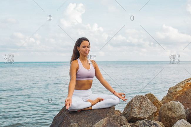 Woman meditating on rock by the ocean
