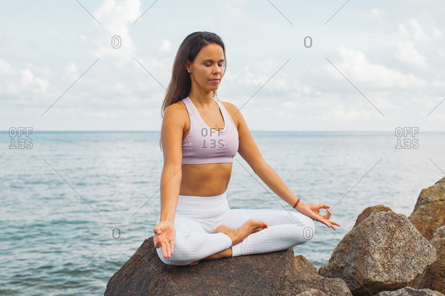 Woman meditating on rock by the sea
