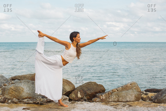 Happy woman doing yoga pose by the ocean