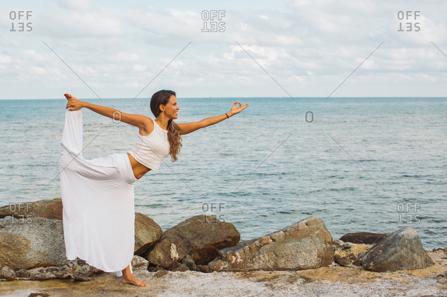 Happy woman doing yoga by the ocean