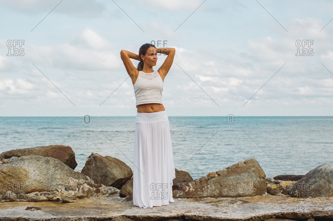 Woman wearing white standing by the ocean