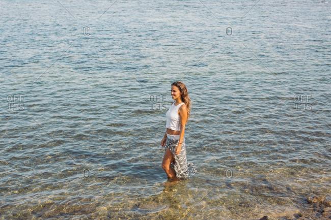 Brunette woman standing in the ocean looking away