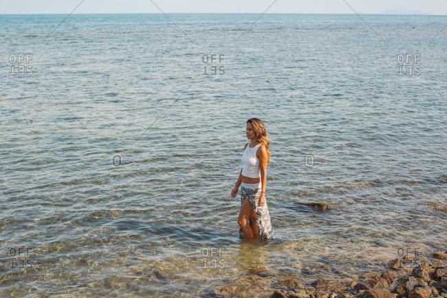 Brunette woman standing in the ocean tide looking away