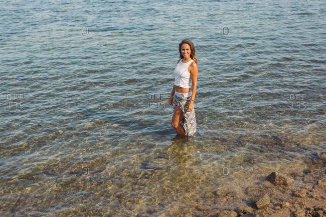 Brunette woman standing in the ocean