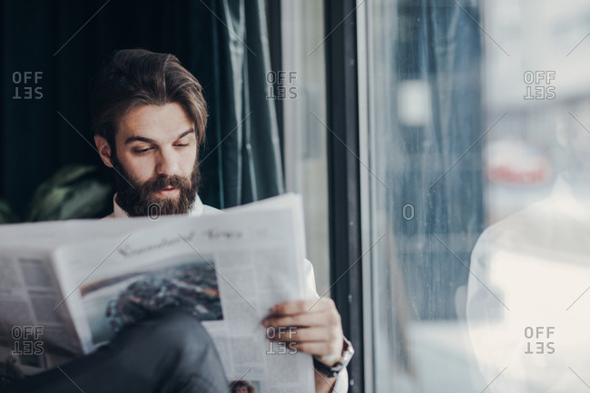 Businessman with beard reading newspapers at cafe