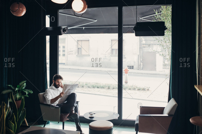 Caucasian businessman reading newspapers at cafe