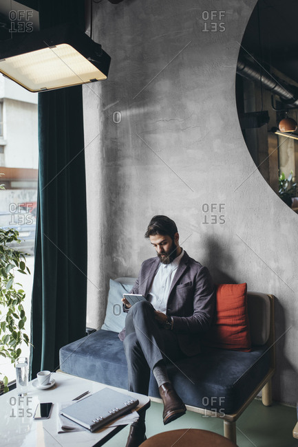 Stylish caucasian businessman working on tablet at cafe