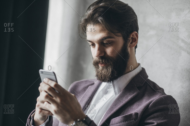 Businessman with beard typing on cell phone