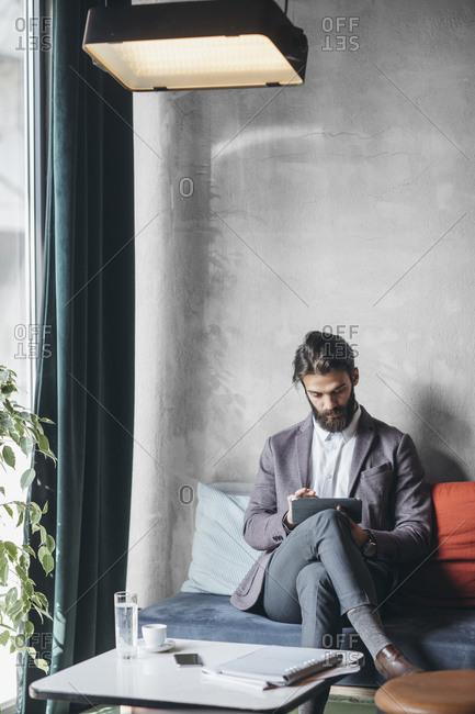 Elegant caucasian businessman reading on tablet at cafe