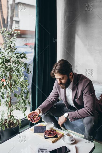 Stylish businessman eating breakfast at coffee shop