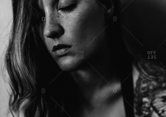 Monochrome portrait of solemn woman with eyes closed