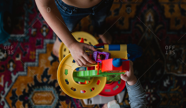 Overhead view of brothers playing with toy cars in living room