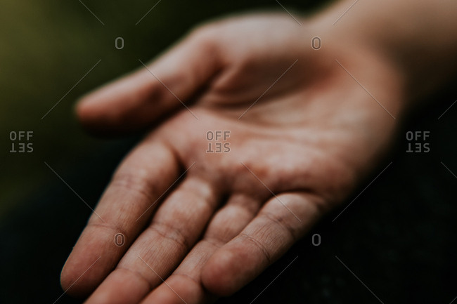 Detailed closeup of child's dirty palm playing outside