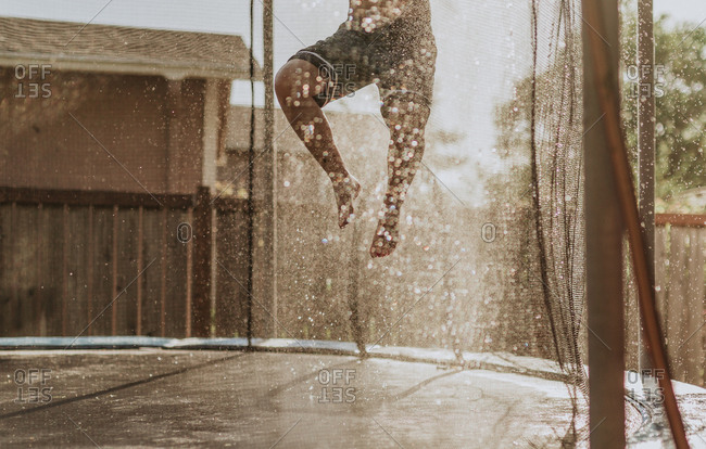 Cropped view of boy leaping on trampoline over sprinkler