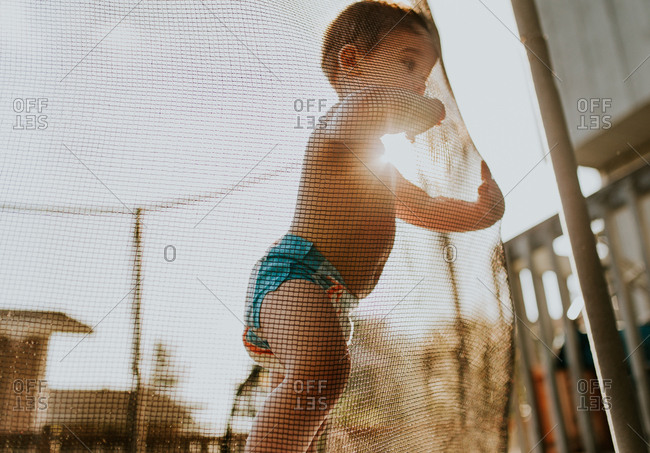 Curious toddler leaning on trampoline net at sunset