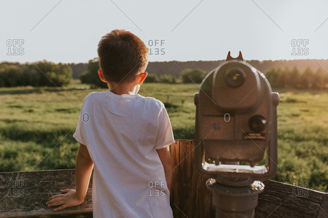 Back view of adolescent boy looking across scenic field
