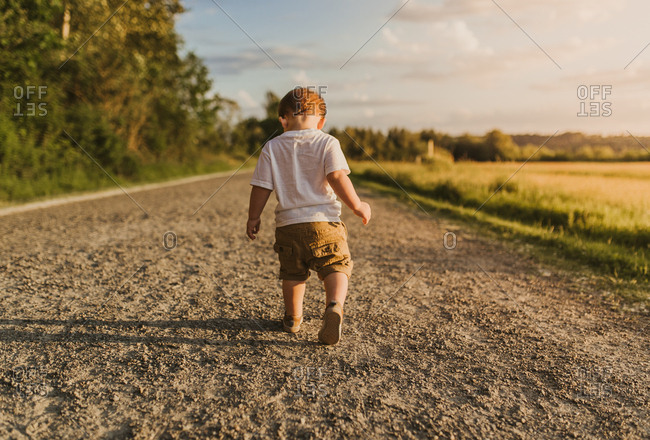 Back view of toddler boy roaming rural road at dusk