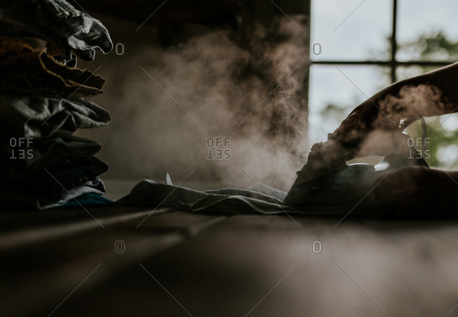 Hand holding steamy iron in dark laundry room
