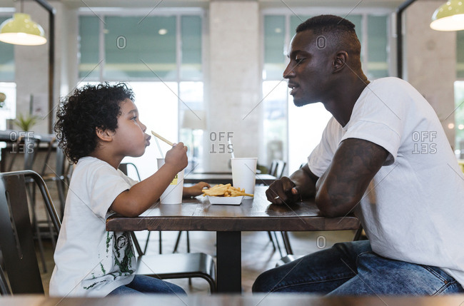 An african father and his son eating fast food