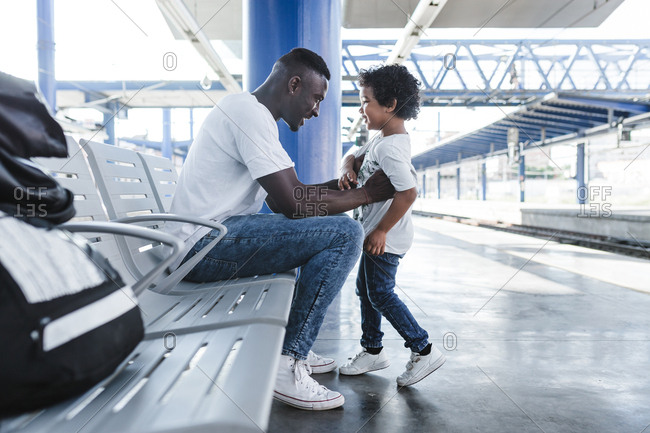 An african father and his son waiting for the train on the train station