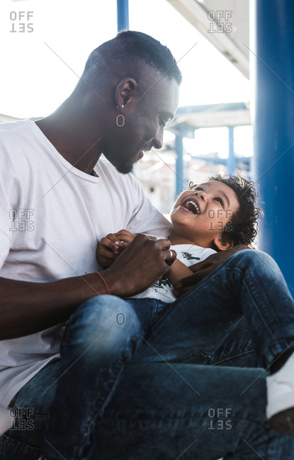 An african father tickles his little child