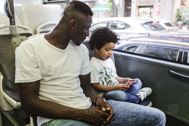 An african father using his phone while his son watches the screen on a bus