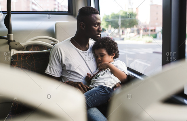 An african father has his son asleep in his arms