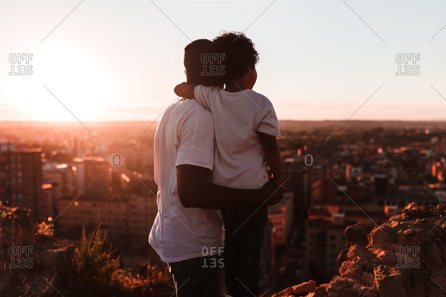 Rear view of an african father and his son observes the city horizon