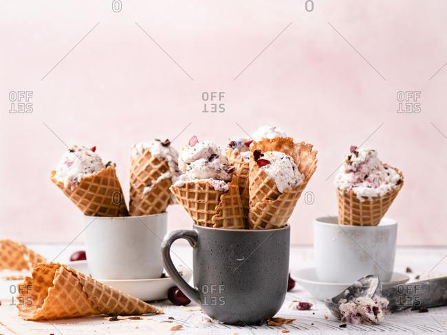 No churn vanilla ice cream with dark chocolate and cherry chunks in waffle cones.