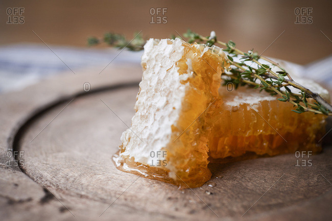 2 large pieces of honeycomb with fresh thyme on a rustic wood plate.