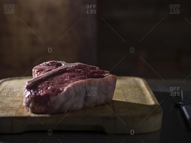 A raw t-bone steak on a rustic, butcher block cutting board.